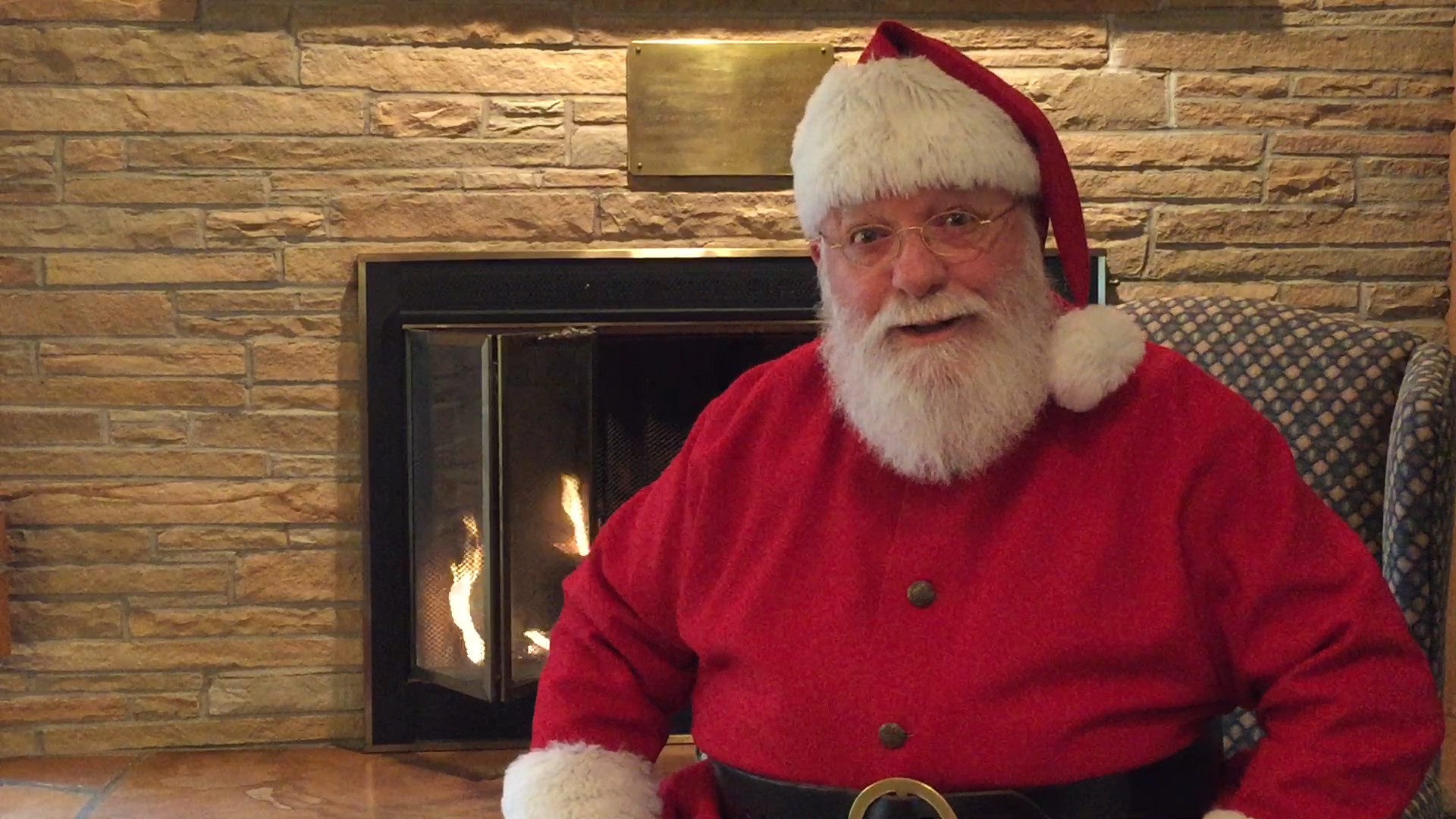 Santa relaxes in front of his fireplace