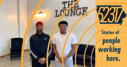 proprietors of the lounge barbershop standing in front of a couch