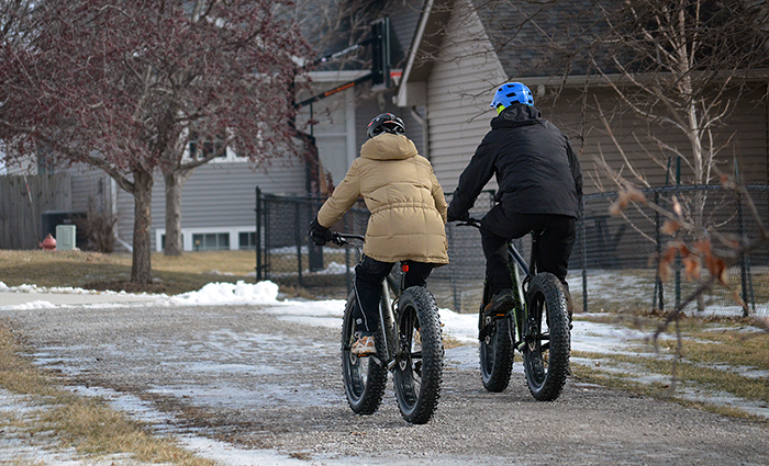 To fat-tire bike riders head away on a gravel path in winter.