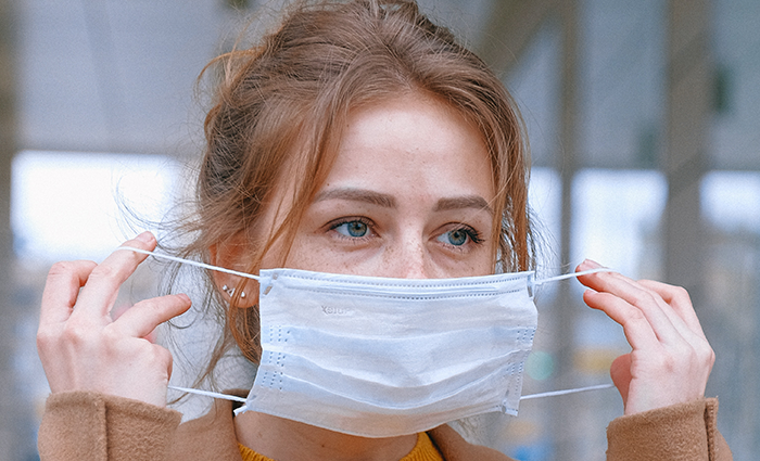 A woman putting on a mask to protect herself and others from coronavirus