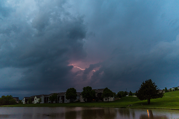 Lightning over homes and a lake in North Liberty by Elizabeth Pearson;
