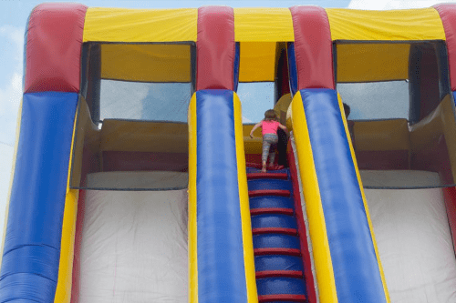 kid climbing up inflatable slide