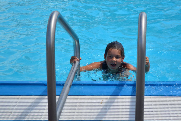 A young swimmer climbs out of the water at the North Liberty outdoor pool.