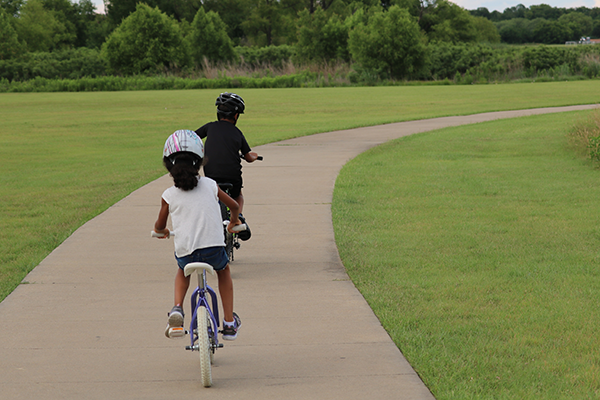 Children ride bikes on a bike path with trees in the distance.
