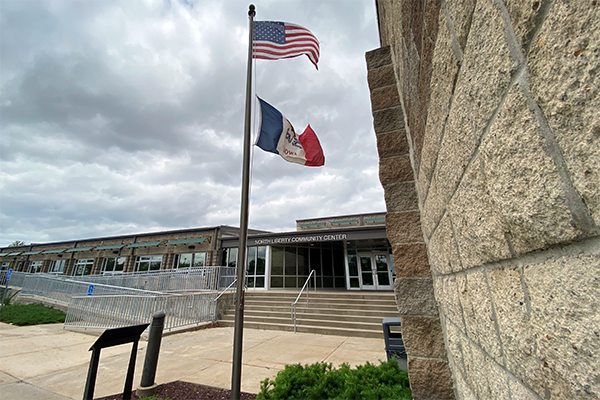 The south face of the Community Center with Iowa and United States flags flying.