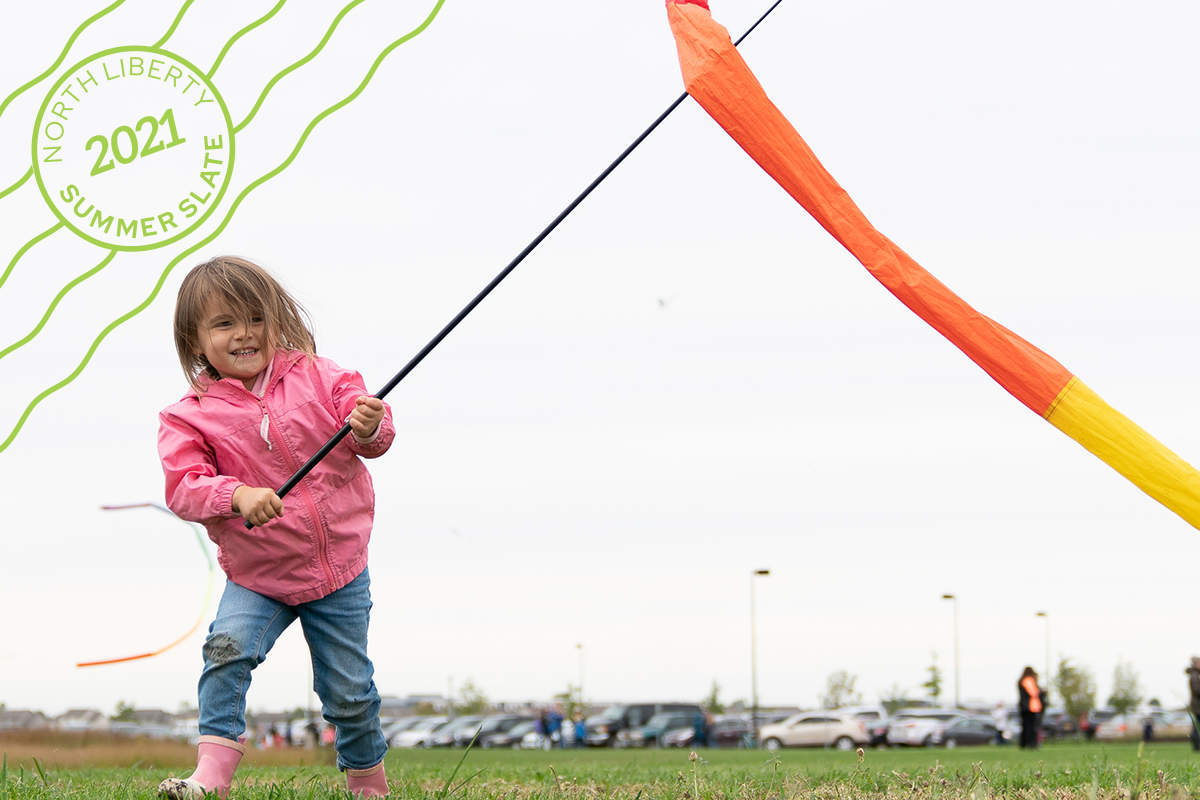 Kid playing with kite ribbon outside