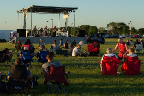 people on lawn chairs watching a stage