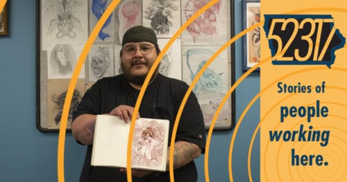 tattoo artist standing amidst his drawings