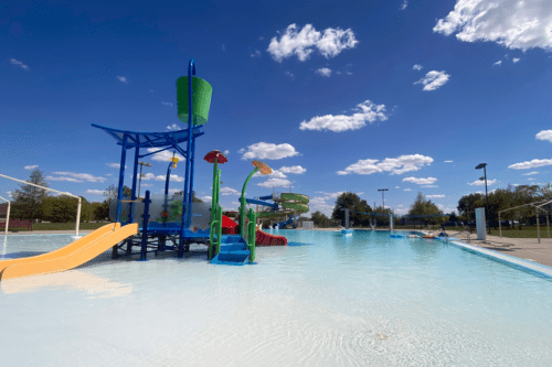 A wide-angle photo of the North Liberty outdoor pool under clouds and blue sky
