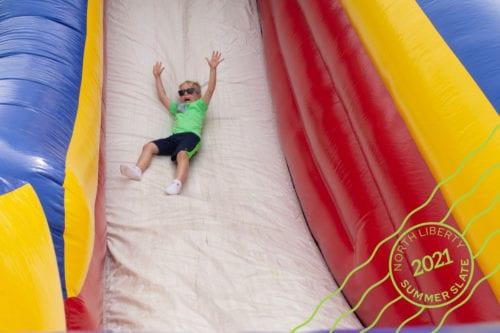 a kid going down an inflatable slide
