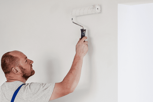 A man paints a house wall with a roller.