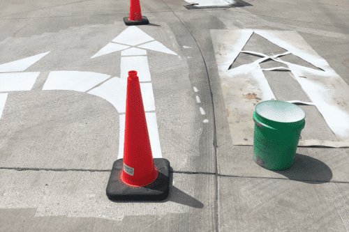 Orange cones protect freshly painted large arrows on a street. A stencil lays nearby.