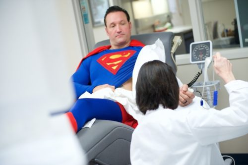 A man, dressed as Superman, donates blood